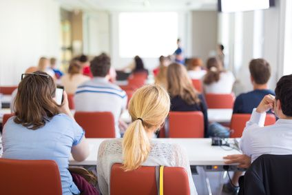 Speaker giving presentation in lecture hall at university. Participants listening to lecture and making notes.